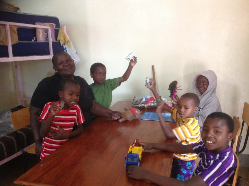The house matron and 5 children in the orphanage enjoying some toys.
