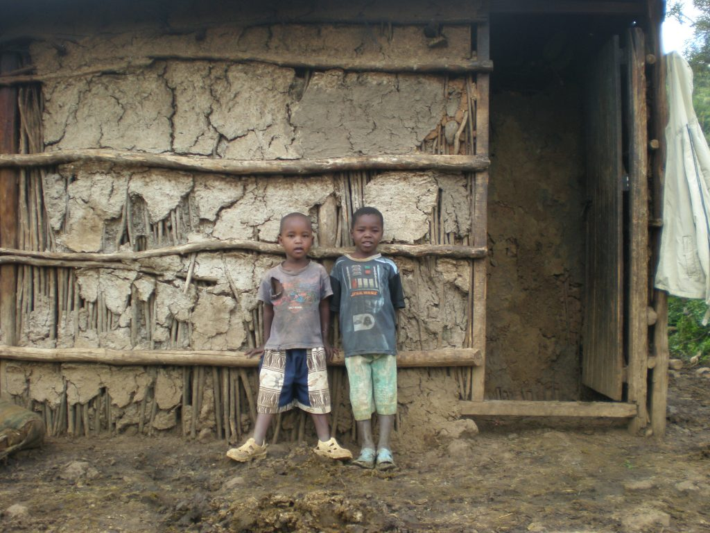 Dadio and Joshua outside their hut.